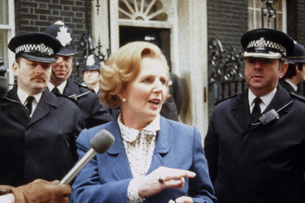 Margaret Thatcher arrives at Number 10 Downing Street in 1979. She is flanked by two policemen and is speaking to a microphone.