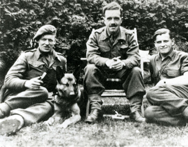 Members of 13 Parachute Battalion relax with a Para dog 1945