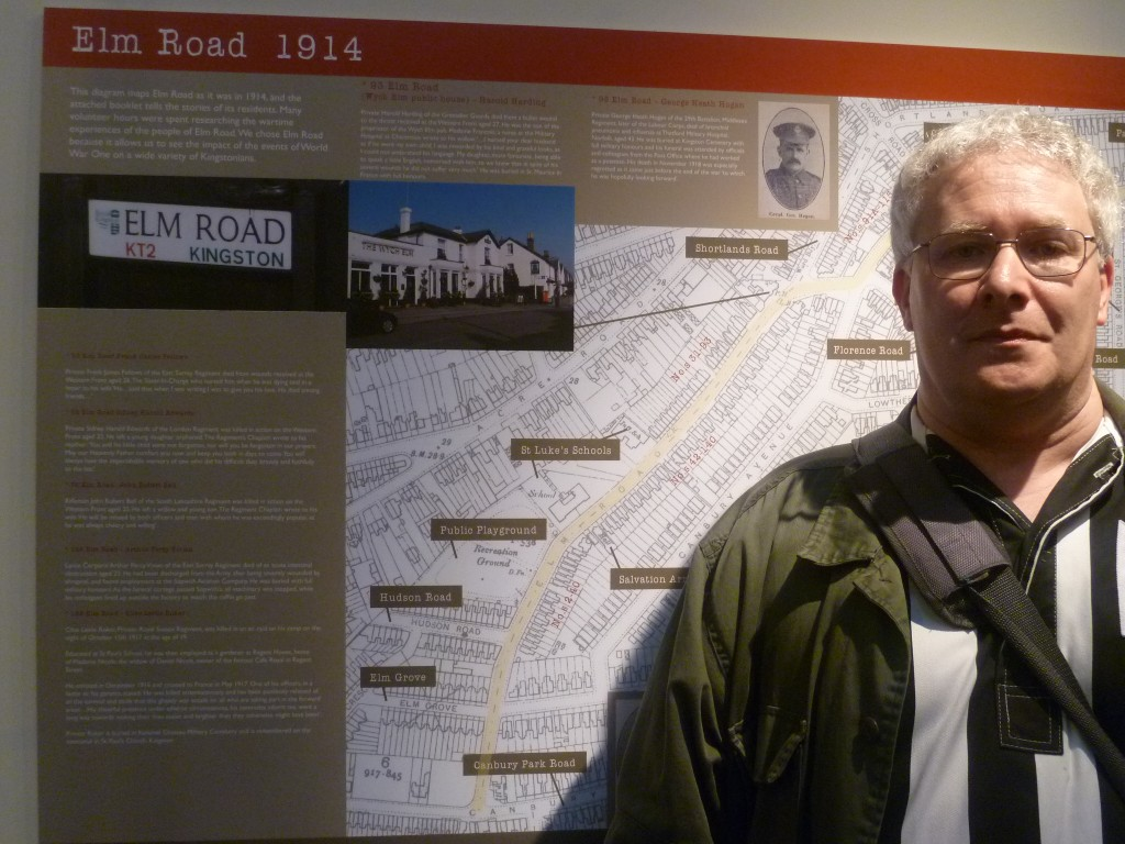 A photograph of one of Kingston Museum's volunteers, Dan Leissner, standing in front of a map of Elm Road containing information about the lives of its residents in 1914-1918.