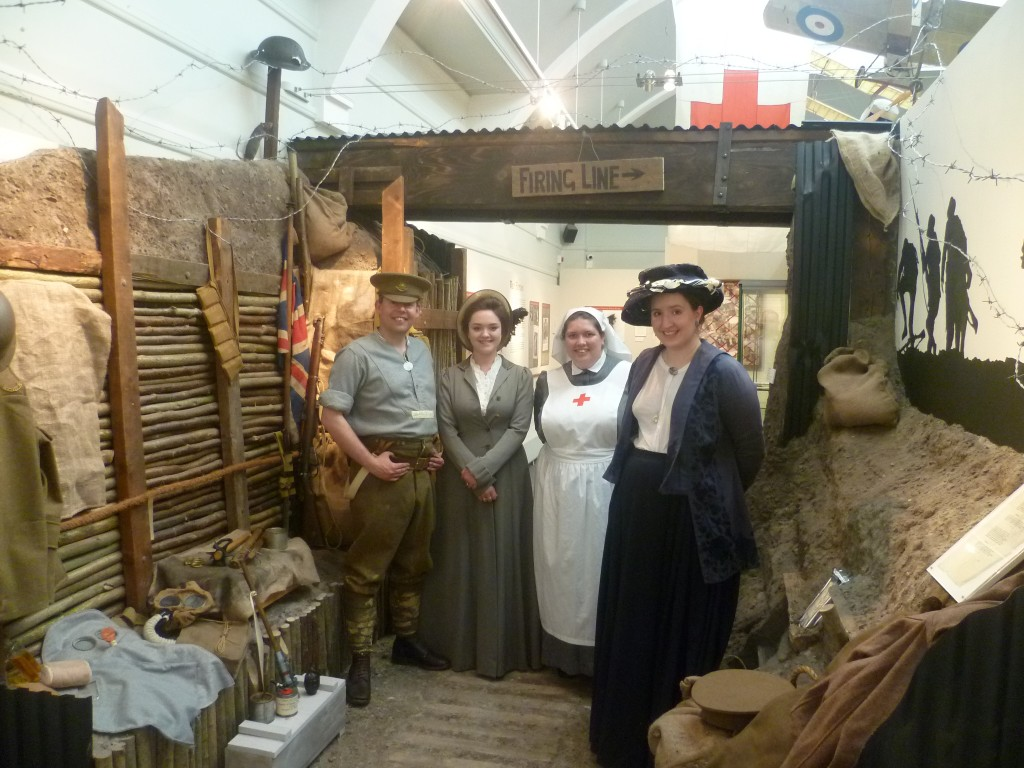 A photograph of two re-enactors dressed as a Tommy and a VAD nurse and two members of the museum staff dressed in Edwardian costume. The photograph is taken in the trench exhibit which is part of the exhibition.