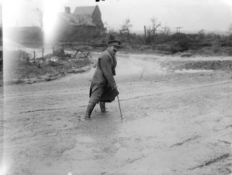 First Official War Artist Muirhead Bone crossing a muddy river, dressed in trench coat with scarf and walking cane. Maricourt, September1916.