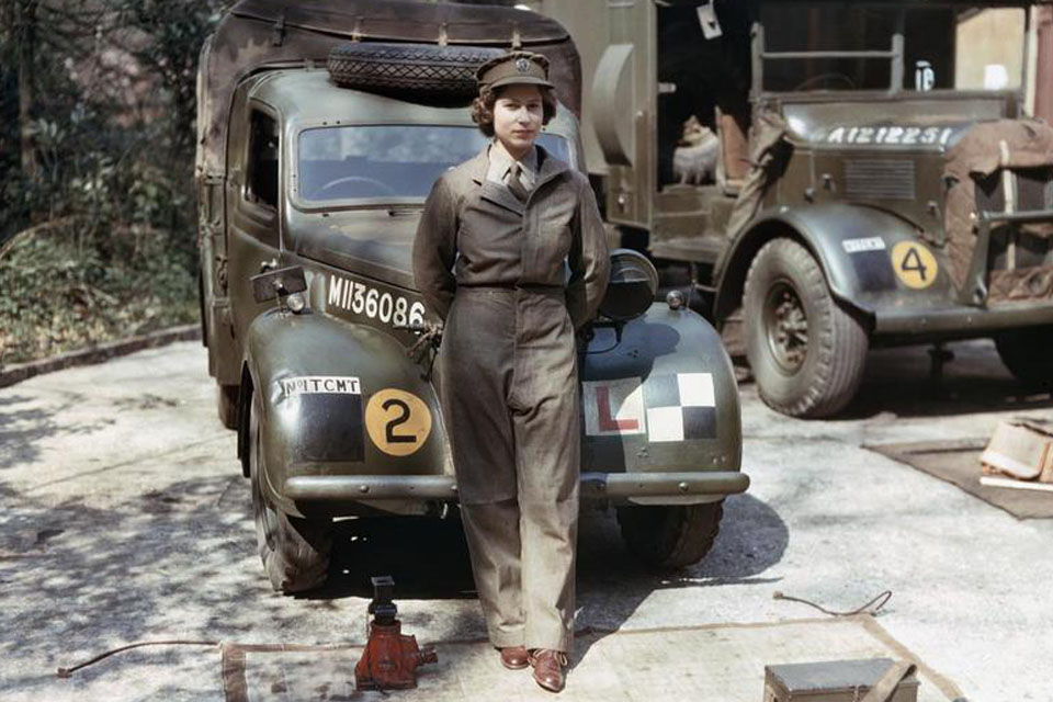 Princess Elizabeth, a 2nd Subaltern in the Auxiliary Territorial Service (ATS), wearing overalls and standing in front of an L-plated truck.