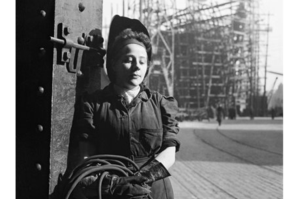 A study of a young woman welder. In the background a ship under construction in a slipway can be seen.