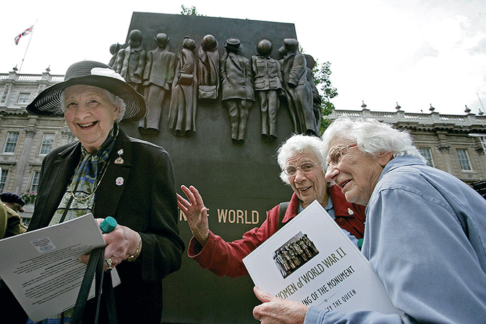 Three women in front of the Monument to the Women of World War II, a British national war memorial situated in Whitehall in London