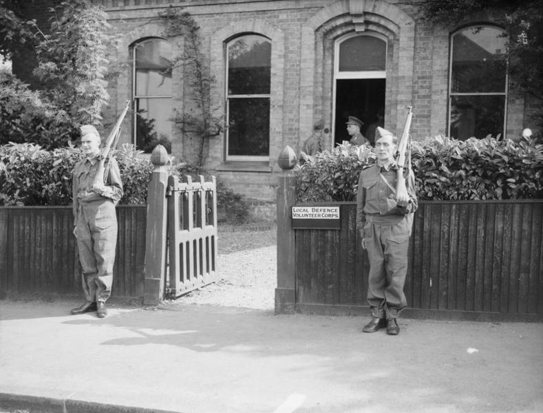 Two members of the Local Defence Volunteer Corps, bearing rifles and standing guard outside a building. An officer can be seen talking with another one of the ranks near the entrance.
