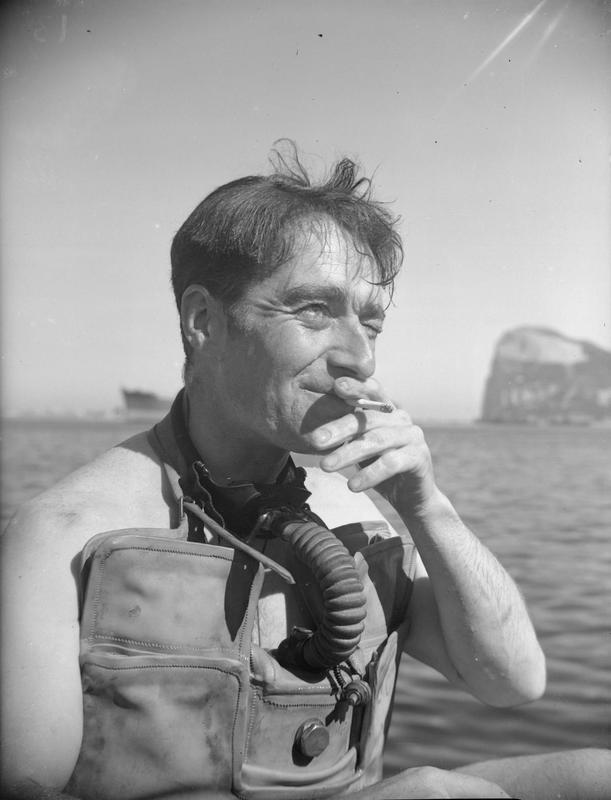 "Commander Lionel ""Buster Crabb sat in a boat beside the sea. Smoking"