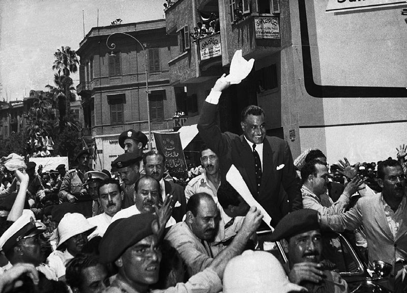 Egyptian president Gamal Abdel Nasser is being met and standing within a cheering crowd.