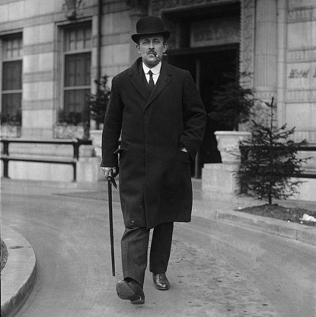 Sir Maurice Hankey is striding with a sense of purpose. He is wearing a bowler hat, smoking a pipe and carrying a walking stick.
