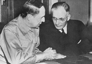 Posed together: Australian PM John Curtin with US General Douglas MacArthur at a War Council meeting in Canberra. They are close together, discussing matters.