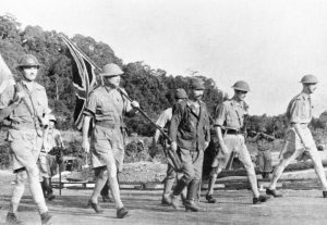 Soldiers in shorts and shirts, walking towards the enemy (Japan), holding a British flag.