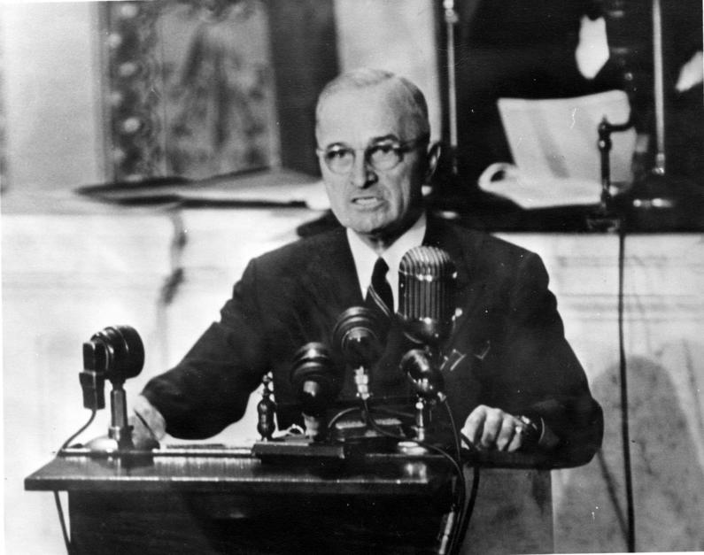 Truman Doctrine clothed smartly, sat at a desk, equipped with microphones on the table. Ready to record a message