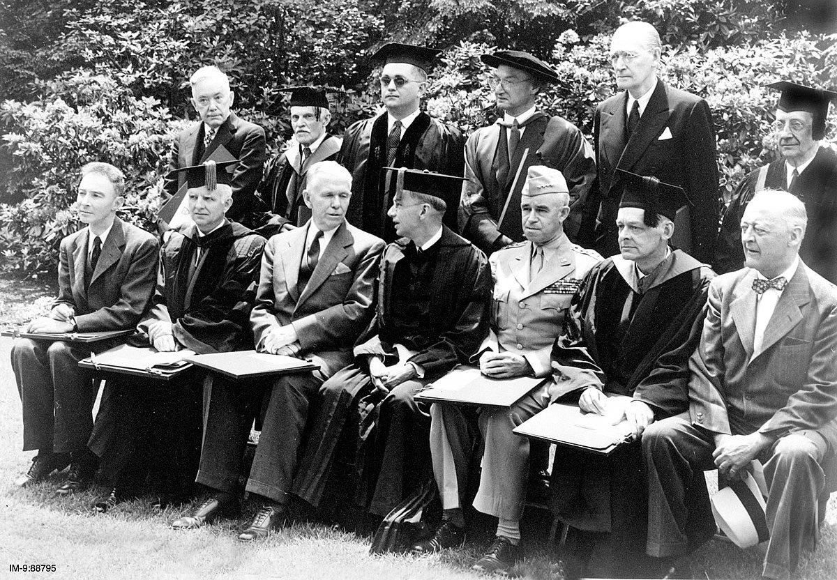 A class of elderly gentlemen, dressed in graduation robes which are about receive honorary degree at Harvard.
