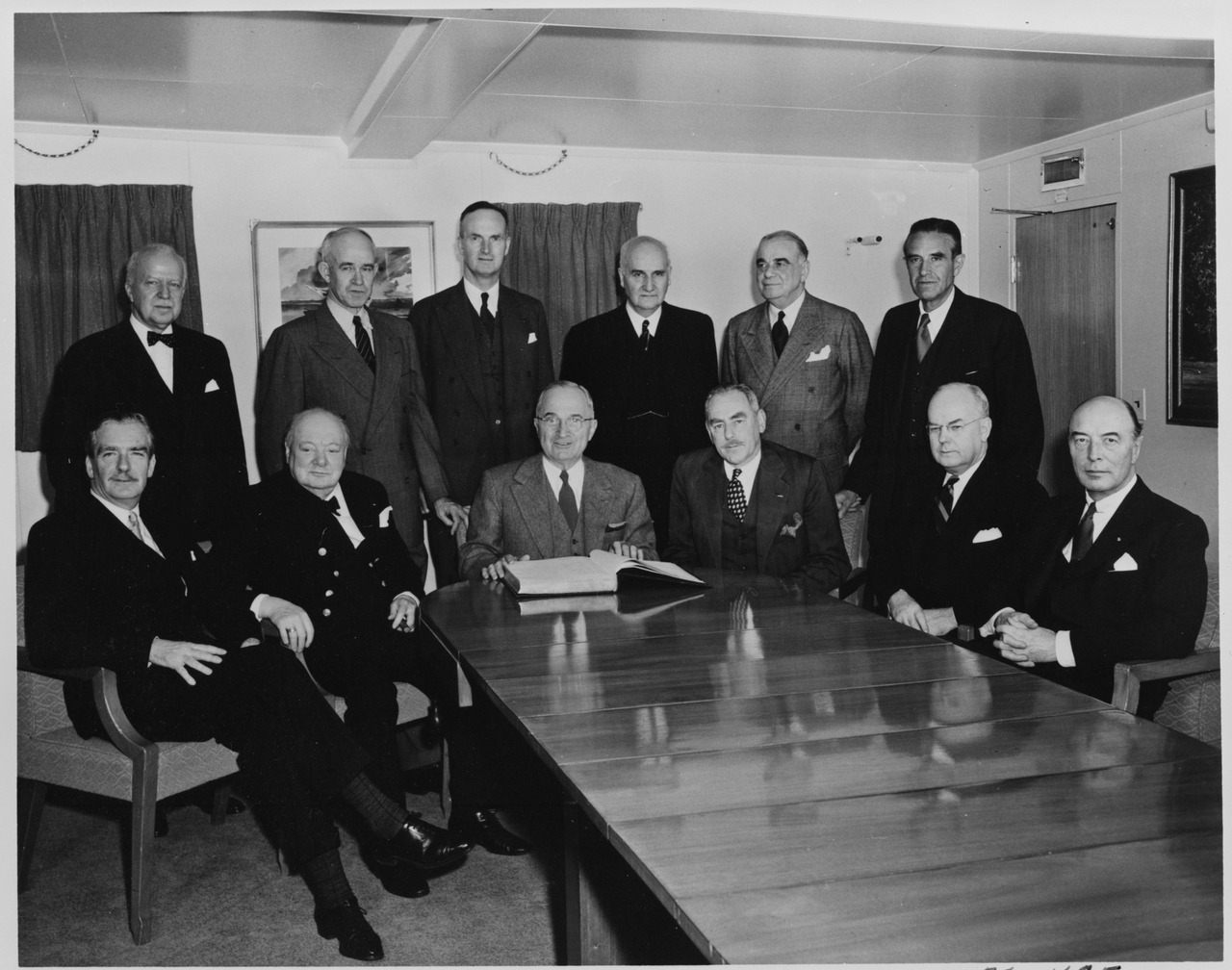 Posing are participants in a conference aboard President Truman's yacht, Oliver S. Franks (third from left, standing), Baron Franks (1905-1992), with Prime Minister Winston Churchill and US President Harry S. Truman. They are huddled around a table.