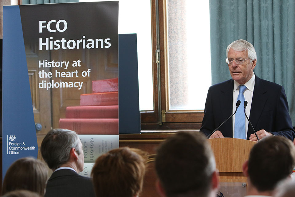 Sir John Major in front of a crowd, listening to him about Homosexuality in the FCO. Alongside the FCO Historian Banner - 'History at the heart of diplomacy'