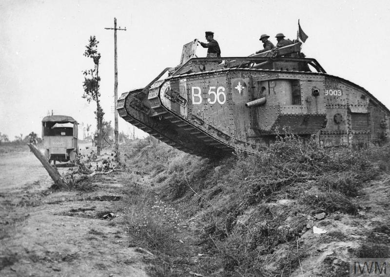 A war tank passing over a trench, looks like a warzone in 1918