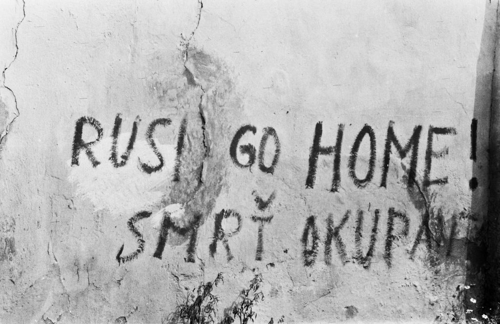 A black and white picture of a wall with graffiti on it saying: Rush go home! smrt okupant