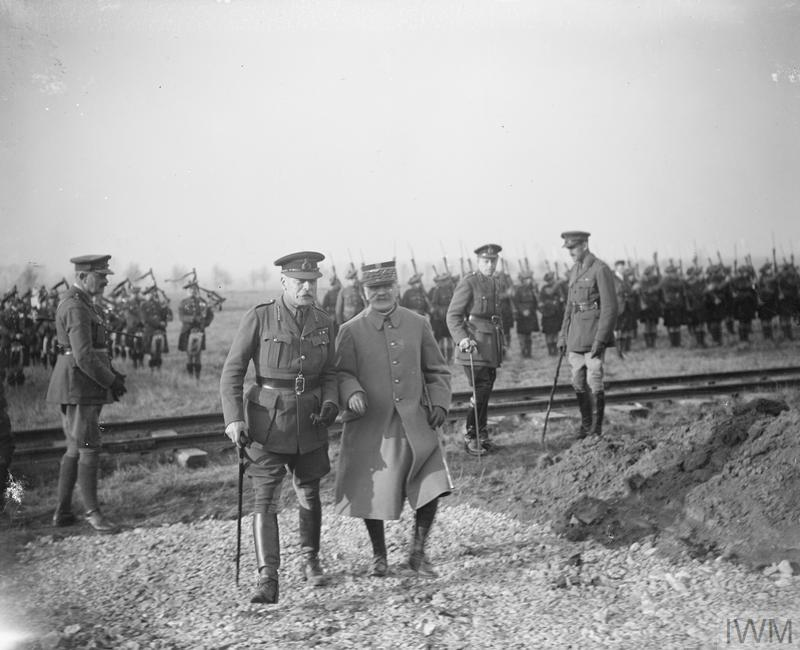 The picture displays 2 men walking and discussing, looking like they discussing what is in front of them. They are surrounded by younger soldiers in formation.
