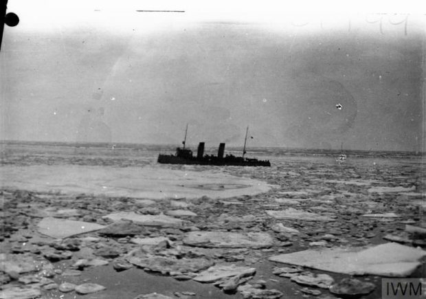 An old black and white picture of a boat in the middle of an icy water.