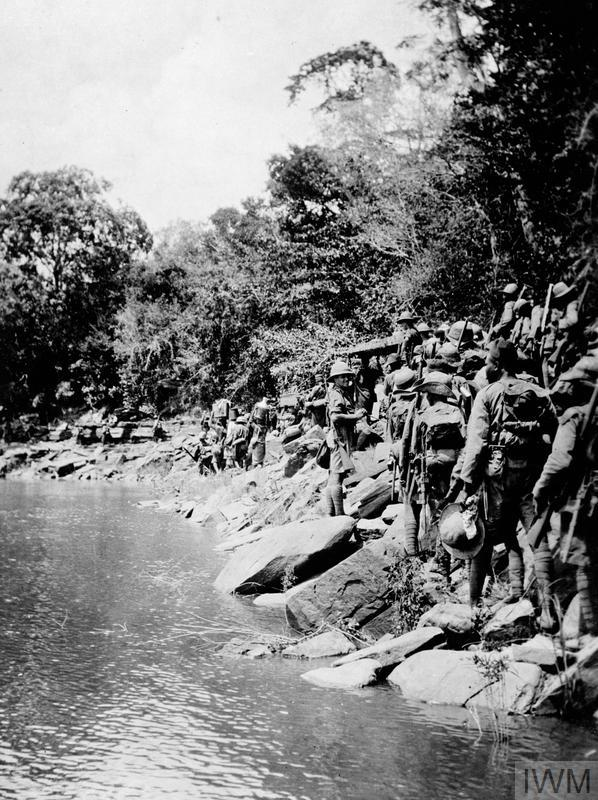 Black and white picture of soldiers along a river. They are on the move.