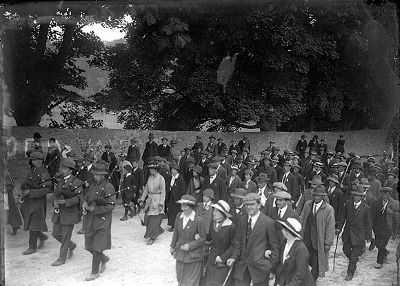 3 bag pipe players leading a crowd of people who are celebrating a victory. Whilst Constance Markievicz is walking in a white coat