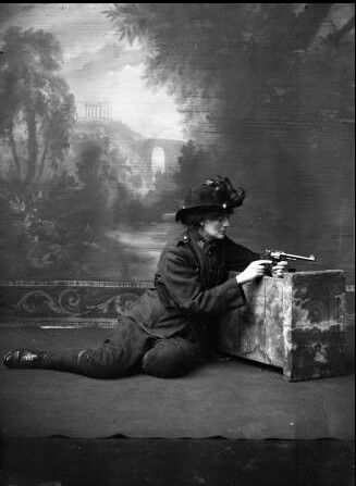 She is kneeling against a studio prop holding a gun, studio full-length portrait