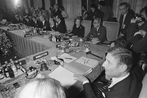 A group of people sat around a table, placed at their assigned places including Thatcher and Carrington