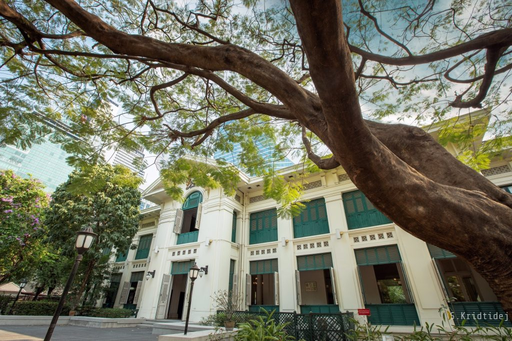 Photograph of the frontage of the British Embassy Bangkok, March 2019 (Kridtidej Sawangcharoen). There is a far spreading tree in the foreground and the Embassy building is very impressive.