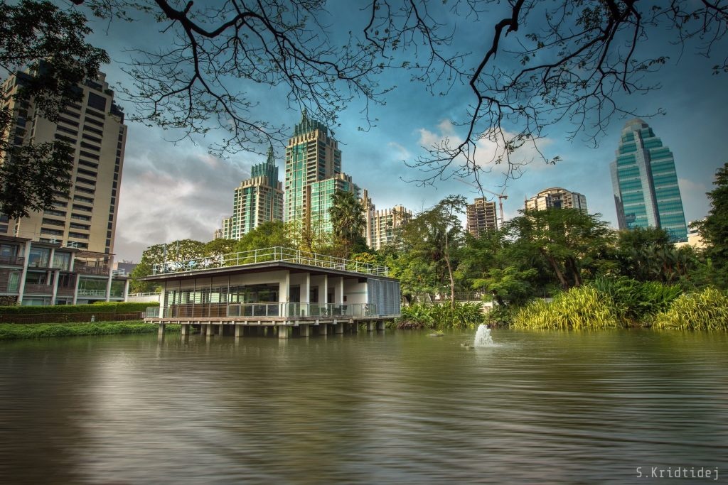 Photograph of the Nai Lert pond, 2019 (Courtesy of Kridtidej Sawangcharoen). A small viewing structure, raised on pillars sits within the pond. A small fountain, within the pond, is also shown. Tall modern buildings dominate the skyline.