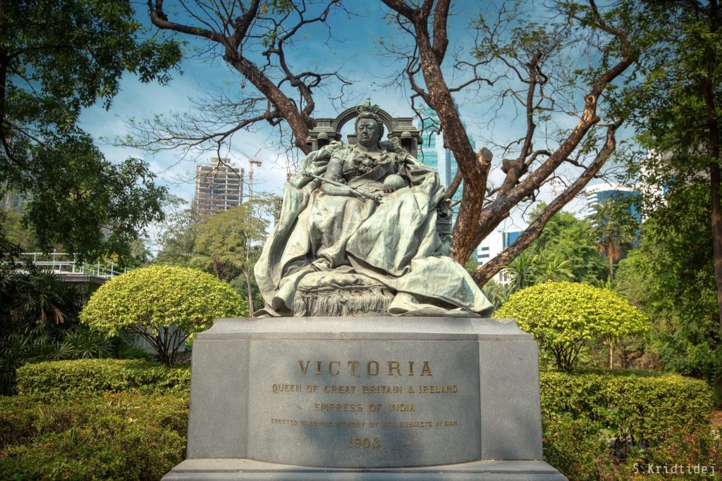 "Queen Victoria Memorial in the compound of the British Embassy Bangkok, 2019 (Courtesy of Kridtidej Sawangcharoen). Queen Victoria is sat on the throne holding the orb and sceptre. The words on the plinth say: ""Victoria, Queen of Great Britain & Ireland, Empress of India. Erected in loving memory by her subjects in Siam, 1903"". The gardens are shown in the background, including a fine example of topiary."