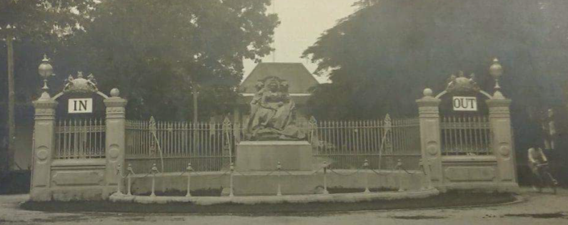 Photograph shows Queen Victoria Memorial at the British Embassy Bangkok (The National Archives, WORK 10/275). The central scuplture shows Queen Victoria sat on the throne. Behind it is a crescent shaped structure made of stone with railings with an 'In' sign attached to arches on the left and an 'Out' sign attached to arches on the right
