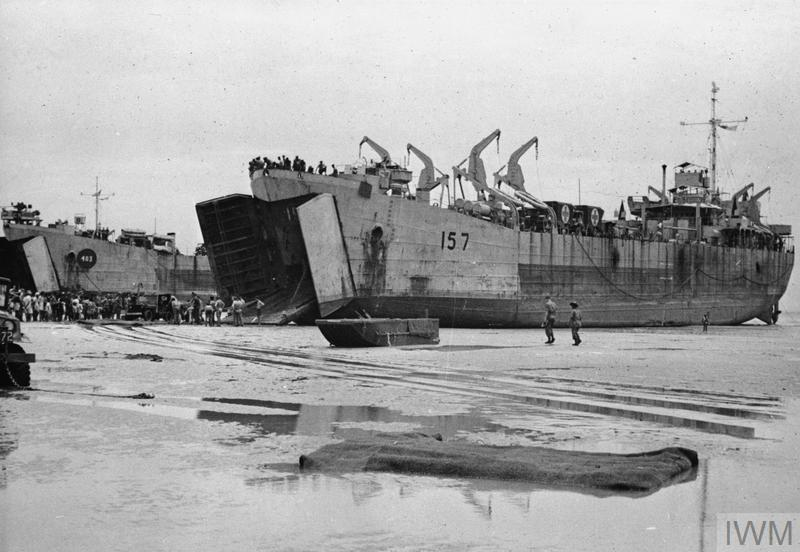 A beached warship, surrounding by soldiers and other debris