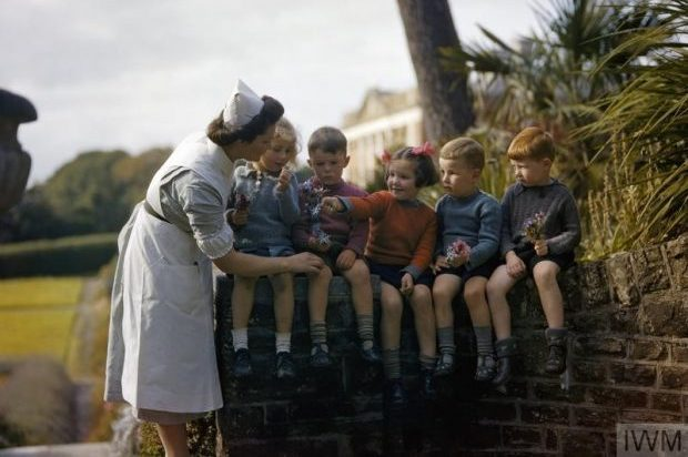 A nurse with child evacuees from Plymouth in the garden of the Chaim Weizmann Home at Tapley Park, Instow, North Devon, October 1942 Five children are shown sitting on top of a wall (two girls, three boys), and a girl in the centre is giving a posy of flowers to a nurse who is wearing a uniform.
