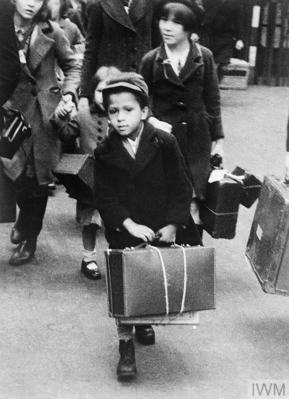 This photograph shows a small black boy carrying his luggage as he left London for the country with a party of other evacuees on 5 July 1940. Source: Imperial War Museum (HU 55936)