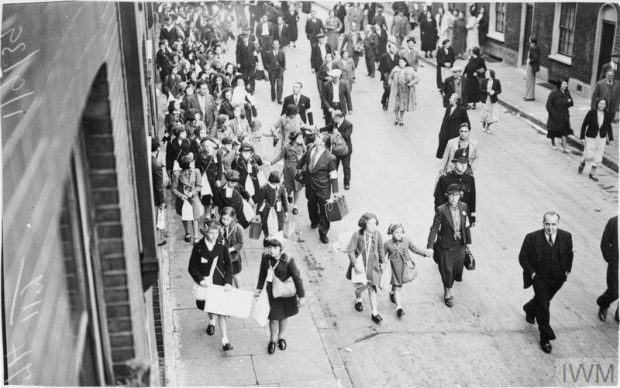 An early start to evacuation is made by children of Myrdle School in Stepney. The children assembled at school at 5am on Friday 1 September 1939. This photograph shows evacuees and adults walking along a street carrying suitcases and gas mask boxes. The adults are wearing arm bands which identify them as volunteer marshals. © Imperial War Museum (D 1939A)