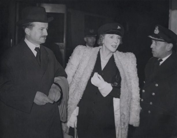 A quintly dressed Alfred Duff and dassling Lady Diana Cooper talking to a VIP.