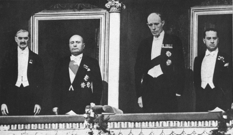 4 men at the opera looking down from a balcony, left to right is Neville Chamberlain, Benito Mussolini, Lord Halifax, and Count Ciano