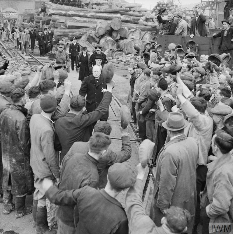 Surrounded by workers, Winston Churchill and Viscountess Astor is cheered by them during a visit to bomb-damaged.