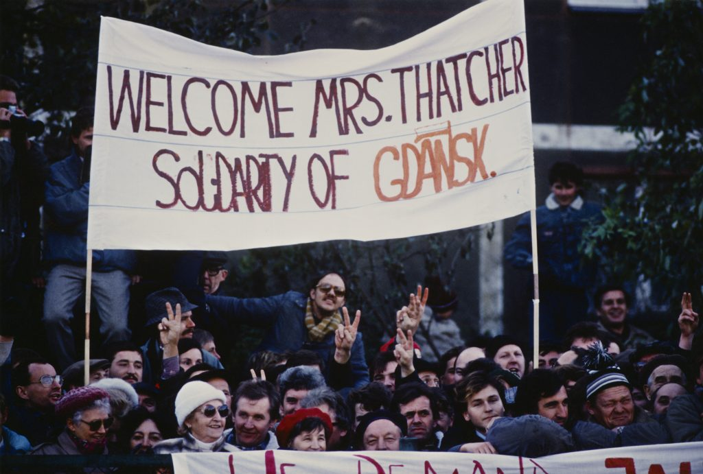 A crowd of people holding up a banner saying: Welcome Mrs. Thatcher Soldarity of Gdansk. People are also holding up peace signs.
