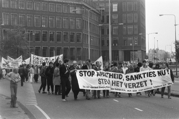 A demonstration march. people are holding a banner saying stop the apartheid