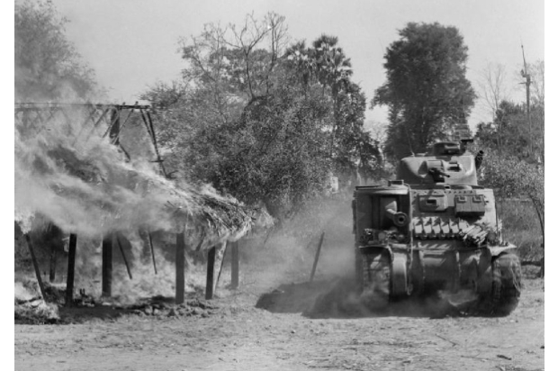 A Lee tank passes a burning building in a Burmese village south of Mandalay, 20 March 1945.