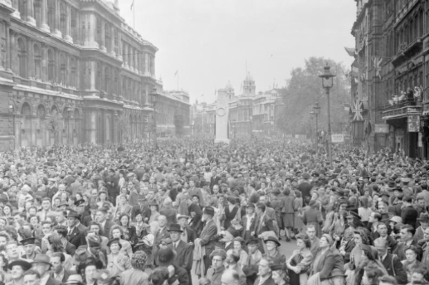 Huge crowds of people are gathered in Whitehall to listen to Churchill's Victory speech and to celebrate Victory in Europe Day. The crowd is a mix of service personnel, civilians and children. Behind them can be seen the Cenotaph.