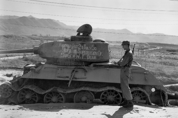 A solder stood next to a captured Russian Tank.