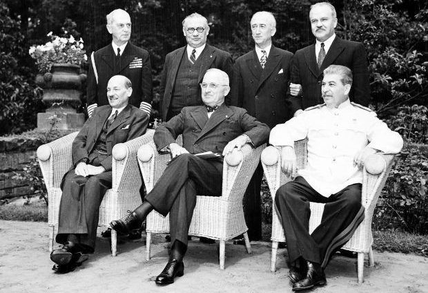 Seated in the garden of Cecilienhof Palace in Potsdam, Germany, L to R: British Prime Minister Clement Attlee, President Harry S. Truman, and Soviet Prime Minister Josef Stalin. L to R, behind them: Adm. William Leahy, British foreign minister Ernest Bevin, Secretary of State James Byrnes, and Soviet foreign minister Vyacheslav Molotov. They are all attending the Potsdam Conference.