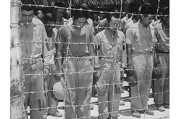 Japanese prisoners enclosed behind barbed wire